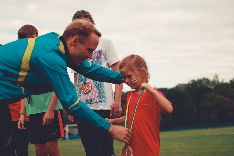 Trenér v AC Choceň předává medaily členům přípravek